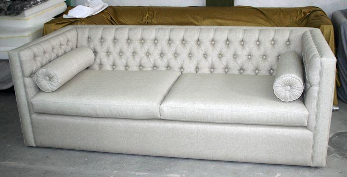 Re tapizado terminado con almohadones cilíndricos con pliegues y botón central de vista en brazo.